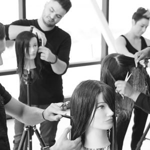 Hairdressing students styling mannequins